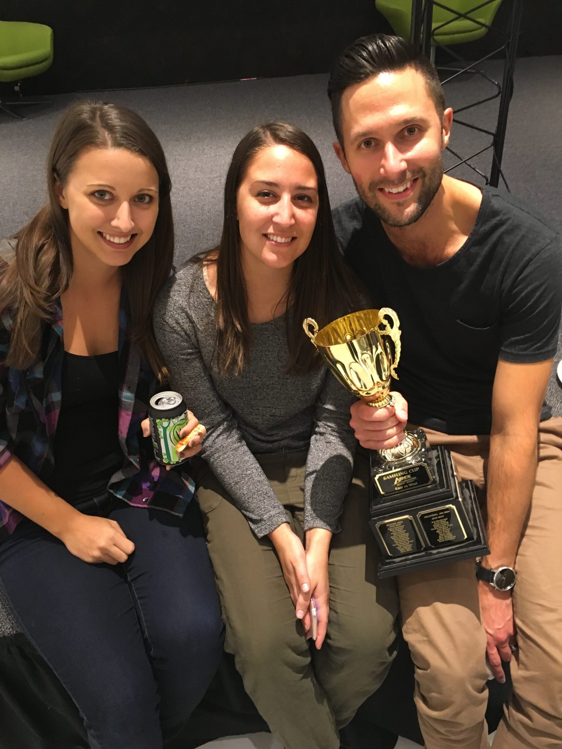 Chad Bennett holding a trophy next to two women